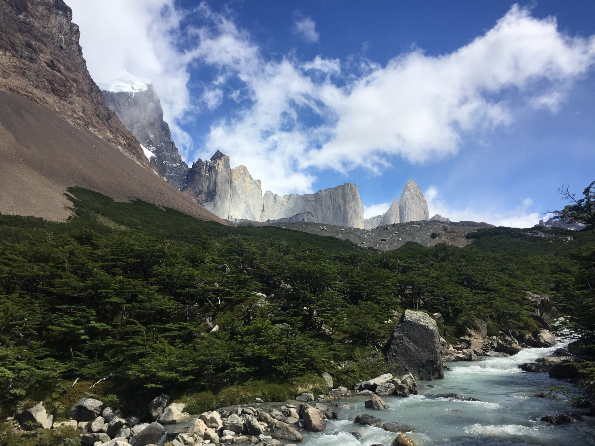 A view or the britanico lookout in torres del paine, chile. There are huge rock faces in the distance sticking straight up out of the ground, blus skies with clouds, and a turquoise river flowing past some large boulders.